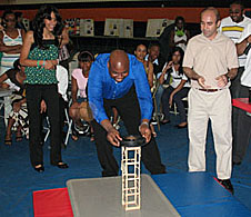 A man sets a heavy weight on a small tower to test a student's design, while mentors look on
