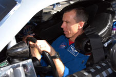 Astronaut Drew Feustel gets ready to drive a NASCAR stock car around the Daytona Speedway.