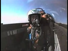 A pilot wears a g-suit in the cockpit of a jet