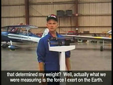 A test pilot stands on a weight scale