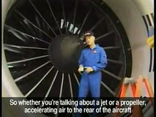 A man stands in front of a large airplane engine