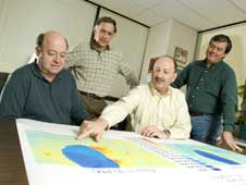 NASA research scientists Jeffrey Luvall, William Crosson, Dale Quattrochi and Maurice Estes, Jr. review a graphic of land surface temperature.