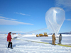 Researchers fill a balloon in Antarctica