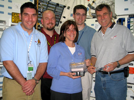 Astronauts and trainers pose for a photo with a plant growth chamber