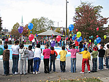 A large group of students standing outside, holding brightly colored balloons