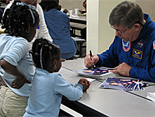 Two girls stand at a table as former astronaut Roger Crouch autographs his picture