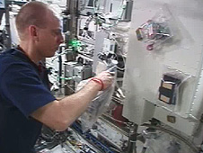 Astronaut Clayton Anderson prepares a plant growth chamber in the space station