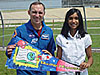 Carl Walz and Tapasya hold a pennant in front of the space shuttle on the launch pad