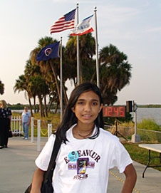 Tapasya stands in front of three flagpoles and a countdown clock