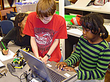 Two students work with a laptop computer and a small robotic vehicle