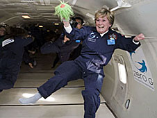 Eileen Poling holds a toy with long green hair as she floats inside of an airplane