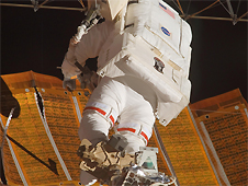 Astronaut working to repair solar arrays on the International Space Station during a space walk