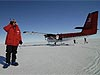 Man in red coat standing in snow next to a red airplane