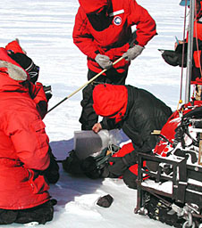 Scientists wearing red coats look at a meteorite lying on the snow