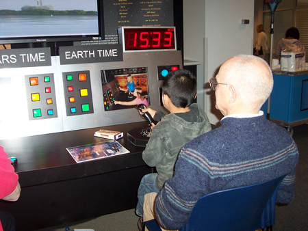 With his grandfather's help, a boy plays Mission Director for the Ares Mars airplane using NASA's Mars Flight exhibit. Ares is a concept vehicle for Mars exploration.  Someday, NASA officials could operate the plane remotely from a control center on Earth.