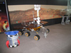 Mars rover model with meteorite Elephant Moraine 79001 in the background.