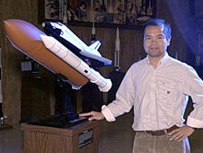 Bruce Vu stands next to a model of the space shuttle