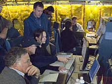 Scientists and telescope operators focus on data readouts set up inside NASA's SOFIA airborne observatory during telescope characterization tracking tests.