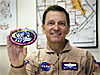 NASA Dryden pilot and artist Mark Pestana holding the STS-123 patch he designed