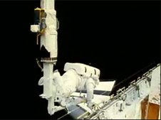 An astronaut attached to the space shuttle's robotic arm working in space