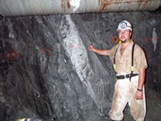 Scientist Duane Moser stands next to a fracture zone in a South African gold mine