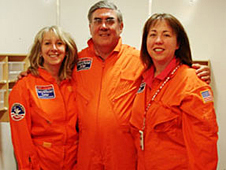 Three teachers in orange flight suits