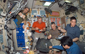 S123-E-007259 --- The STS-123 and Expedition 16 crew members share a meal