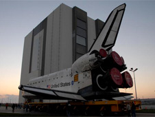 A space shuttle orbiter rolls toward the Vehicle Assembly Building.