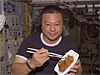 Astronaut Leroy Chiao eats with chopsticks on board the ISS