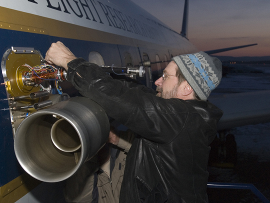 A researcher prepares an instrument on NASA's DC8.