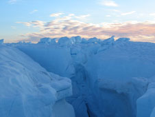 A large fracture is visible in a lake bed on the Greenland Ice Sheet after it drained the lake's entire liquid contents.