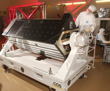 Man in clean room looking at COS instrument