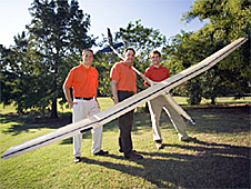 OSU students and their advisor stand outdoors as one student holds the airplane they built
