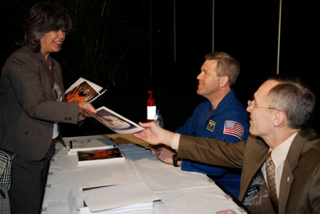 During a break in presentations at NASA's Future Forum in Miami, astronaut Steve Frick and former astronaut Carl Walz sign autographs.
