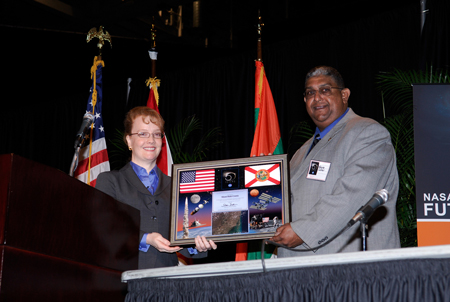 NASA Deputy Administrator Shana Dale (left) presents a 50th anniversary commemorative plaque to Wayne Carter during a Future Forum in Miami that focused on how space exploration benefits Florida's economy.