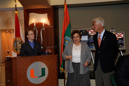 At the luncheon held during NASA's Future Forum in Miami, NASA's Deputy Administrator Shana Dale presents Florida Gov. Charlie Crist (on the right). At center is Donna E. Shalala, president of the University of Miami.