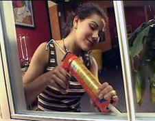 A girl caulks a window