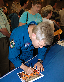 STS-122 Commander Steve Frick signs a crew photograph at Kennedy Space Center.