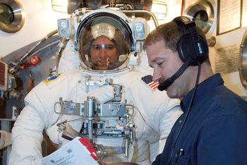 Astronaut Michael T. Good, STS-125 mission specialist, participates in an Extravehicular Mobility Unit (EMU) spacesuit fit check in the Space Station Airlock Test Article (SSATA) in the Crew Systems Laboratory at NASA's Johnson Space Center. Astronaut John M. Grunsfeld, mission specialist, assisted Good.