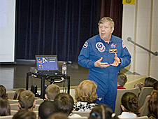 Former astronaut Roger Crouch stands in front of a group of students and teachers