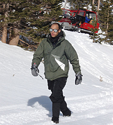 Derrick Lampkin walks along a snow-covered path in a forest