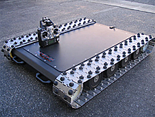A flat rover with silver-colored tracks similar to those of an army tank