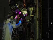 Technicians conduct black light inspection of the Gamma ray Large Area Space Telescope spacecraft a final cleaning.