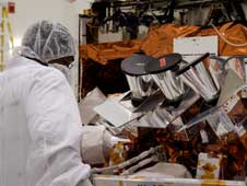 A worker looks over the star tracker sun shades just installed on the GLAST spacecraft.
