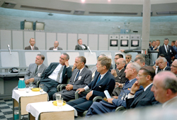 Briefing the chief - President John F. Kennedy receives a briefing in 1962 from Maj. Rocco Petrone (off camera) during a tour of Blockhouse 34 at the Cape Canaveral Missile Test Annex. From left to right: NASA Administrator James Webb, Vice President Lyndon Johnson, director of the Launch Operations Center Kurt Debus, Kennedy, unidentified Air Force General and Secretary of Defense Robert McNamara.