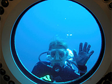 Nyberg in diving gear waving underwater