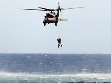 Rescue helicopter hovers over Atlantic Ocean.