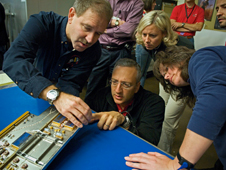 John Grunsfeld and Mike Massimino inspect a new electronics card for the Space Telescope Imaging Spectrograpgh (STIS) instrument