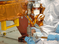 Astronaut Michael Good practices manually overriding a mechanism on the Flight Support System hardware.