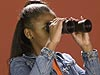 Girl looking through a pair of binoculars